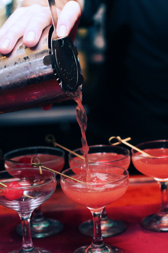 A bartender pours a glass of Bistro Romano's watermelon cocktail.